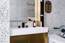 14 The gold vanity and a small shelf add to the look of the bathroom