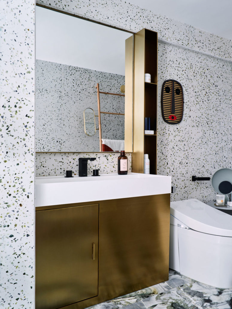 The gold vanity and a small shelf add to the look of the bathroom