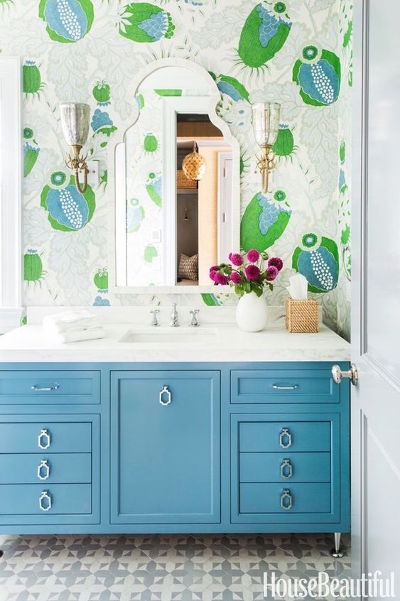 a bright bthroom with colorful and whimsical wallpaper, a blue vanity and bright blooms in a white vase