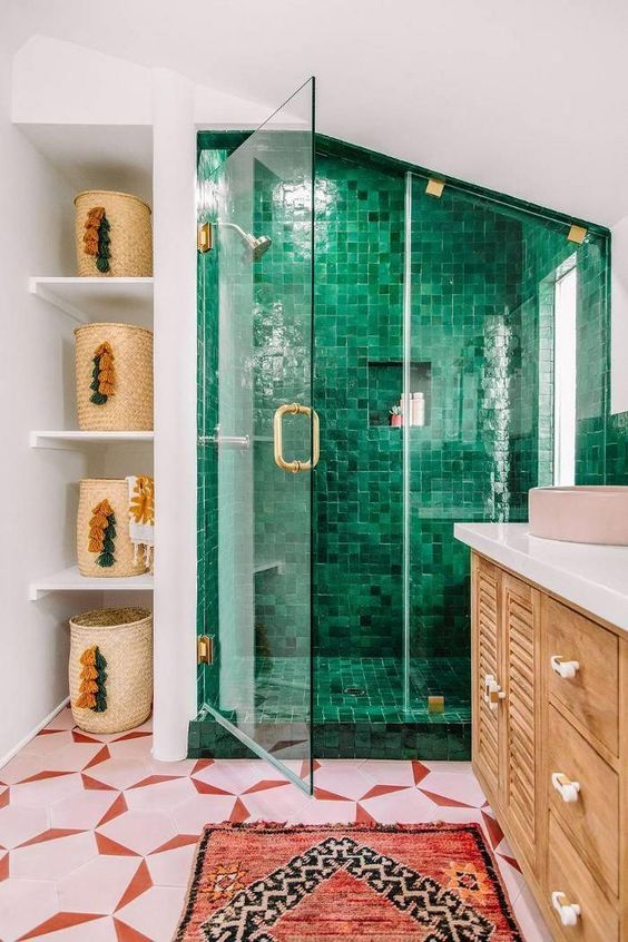 a bright eclectic bathroom design with pink geometric floor and green tile shower, with boho rug and fun tassel baskets