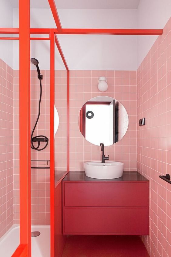 a bright modern bathroom with pink tile walls, a fuchsia floating vanity and orange frames is extra bold