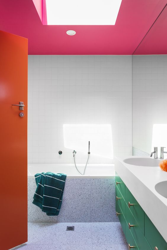 a colorful bathroom with a pink ceiling, an orange door and a green vanity with gold knobs is wow