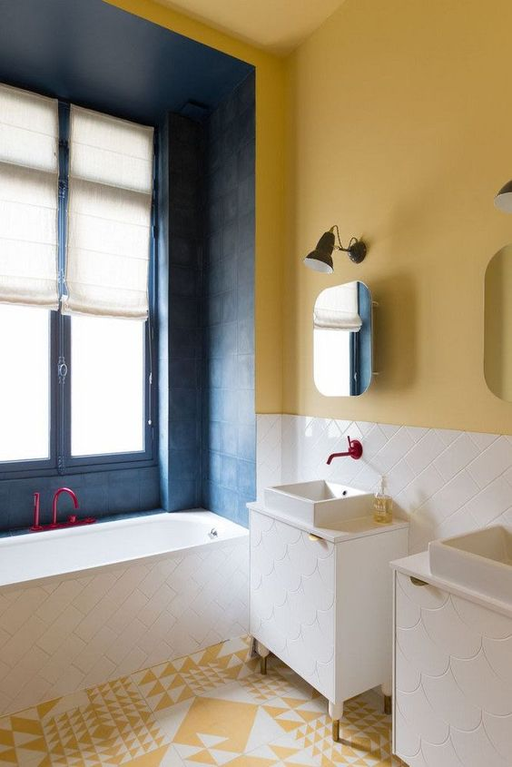 a colorful bathroom with yellow walls, a yellow and white mosaic floor and navy tiles around the bathtub plus fuchsia fixtures