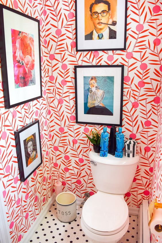 a colorful powder room with bold wallpaper and statement artworks plus statuettes is all about fun