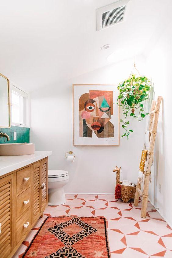 a colorful space with an emerald tile backsplash, pink sinks and lamps and a bright boho rug