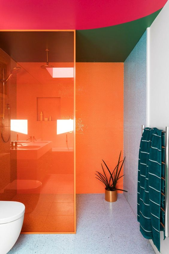 a modernist bathroom in bold orange, green, pink and grey plus teal textiles is a super colorful space