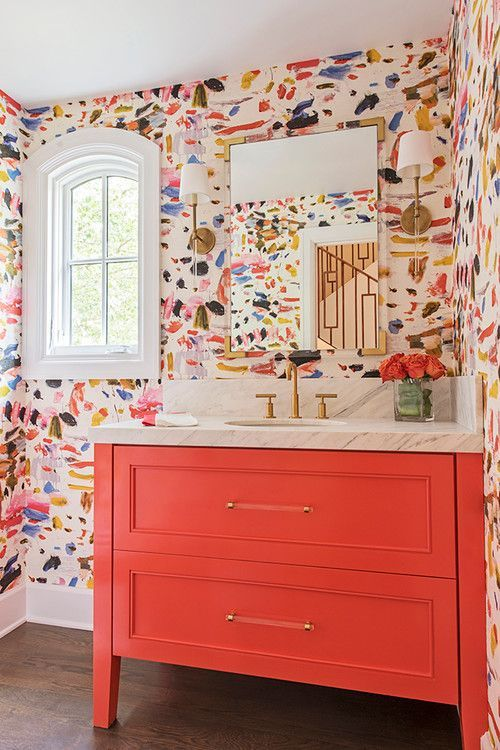a super colorful bathroom with bright brushstroke wallpaper, a coral vanity and bright blooms in a clear vase