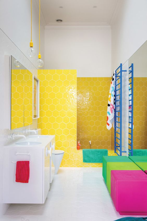a super colorful bathroom with hex yellow tiles, colorful ottomans and bright textiles and a blue radiator