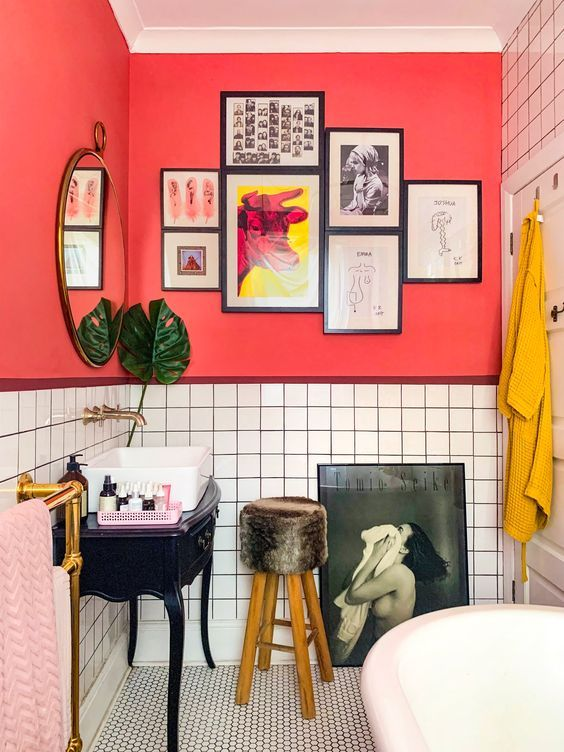 a unique bathroom with red walls, white tiles, pink and mustard textiles and quirky furniture and artworks