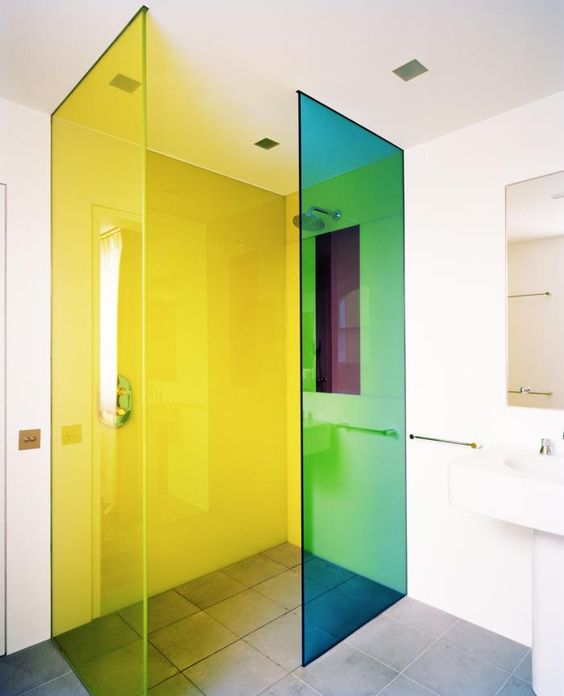 a white bathroom with green and yellow florescent glass shower doors that take over this space