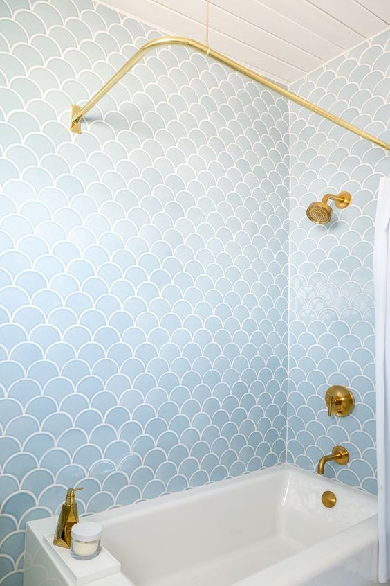 a bathroom clad with light blue fish scale tiles, with chic gold fixtures and accessories looks dreamy and stylish