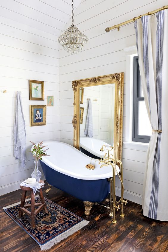 a bathroom covered with white shiplap, with a mirror in an ornate gold frame, artworks, blue tub on gold legs