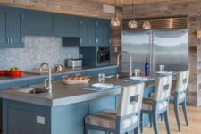 a beautiful blue kitchen with a mosaic backsplash, a concrete countertop, a wooden ceiling and reclaimed wood on the walls