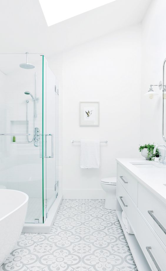 a beautiful white bathroom with a glass enclosed shower space, a large vanity, a mosaic tile on the floor and a large skylight