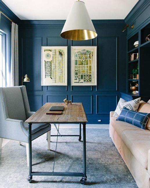 a blue home office with paneling, some comfy furniture, an industrial desk, bold artworks and a catchy white and gold lamp