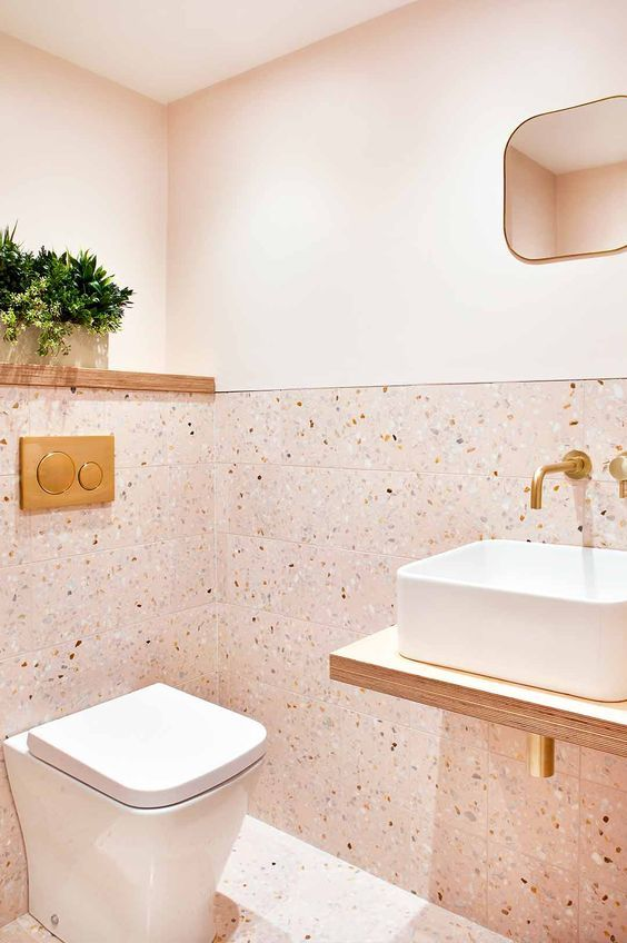 a blush powder room with terrazzo tiles and paint, a floating vanity and gold fixtures and touches here and there
