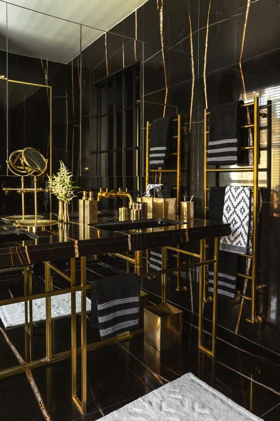 a bold art deco bathroom in black and gold, with marble, metal and lots of graphic touches here and there and gold accessories