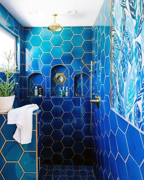 a bold blue bathroom clad with hex tiles and finished with gold grout and gold fixtures is a very chic space