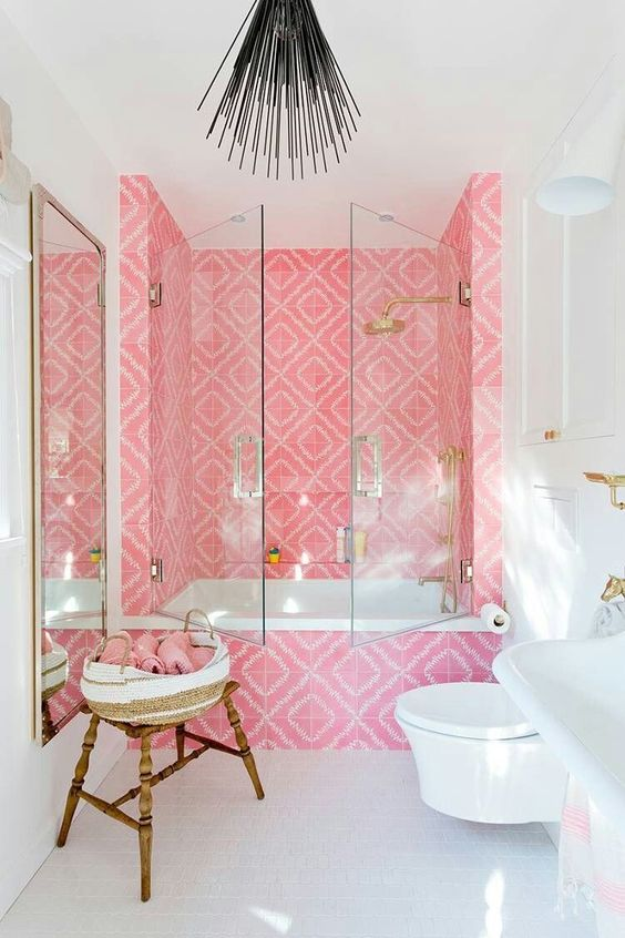 a bold contemporary bathroom with a tub space clad with bright pink tiles, gold fixtures and a mirror in a gold frame