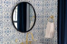 a bold powder room with mosaic tiles on the walls, a navy vanity, a stone sink, a sconce and a black framed mirror
