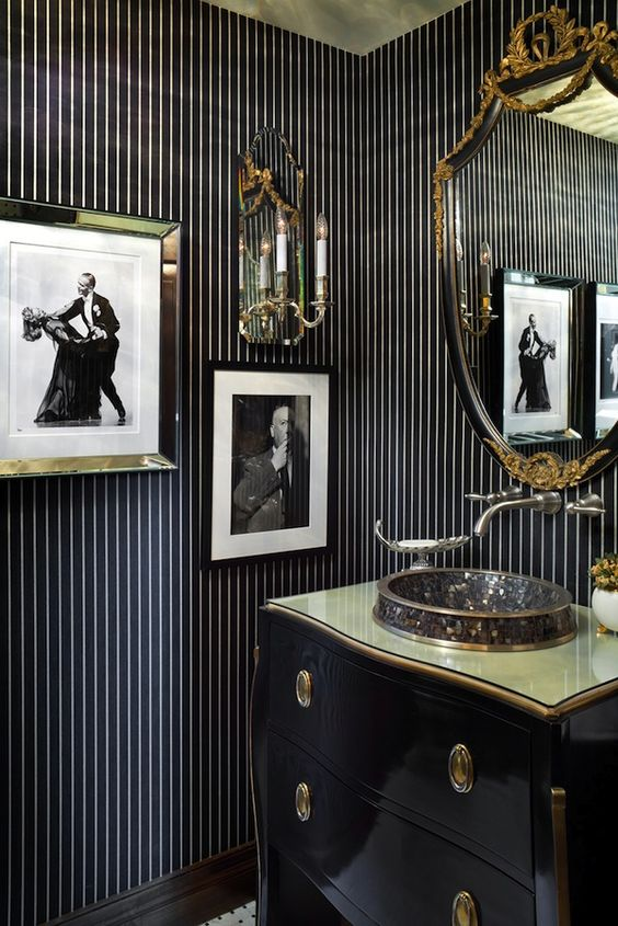 a bold vintage black and gold bathroom with an elegant vanity, a catchy sink, a refined mirror and bold artworks