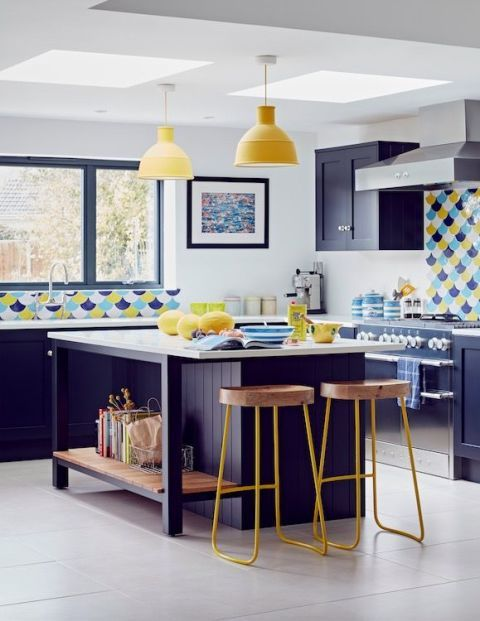 a bright and cheerful kitchen done in bold blue and sunny yellow, with catchy scale tiles and white surfaces for a refresh