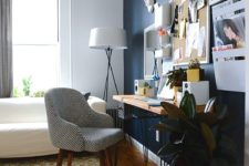 a bright and eclectic home office with a navy statement wall, a bright wlal with art and a pegboard, catchy furniture and a bold rug