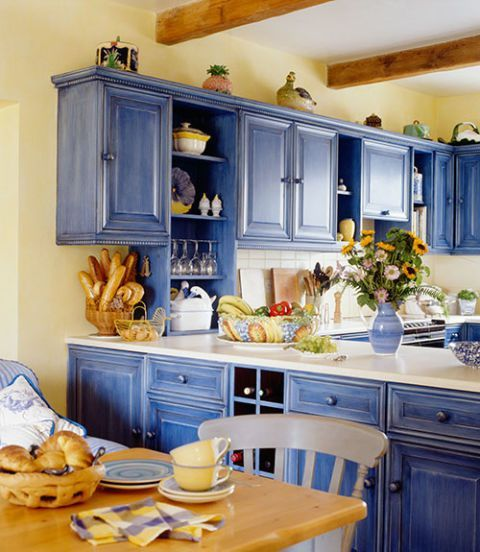 a bright blue and light yellow kitchen refreshed with white surfaces and with light-colored natural wood