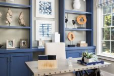 a bright blue home office with a large storage unit that takes a whole wall, a white industrial desk, a white chair and striped curtains