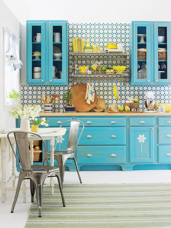 a bright blue kitchen with a bright mosaic tile backsplash and bold touches of yellow here and there is super cool