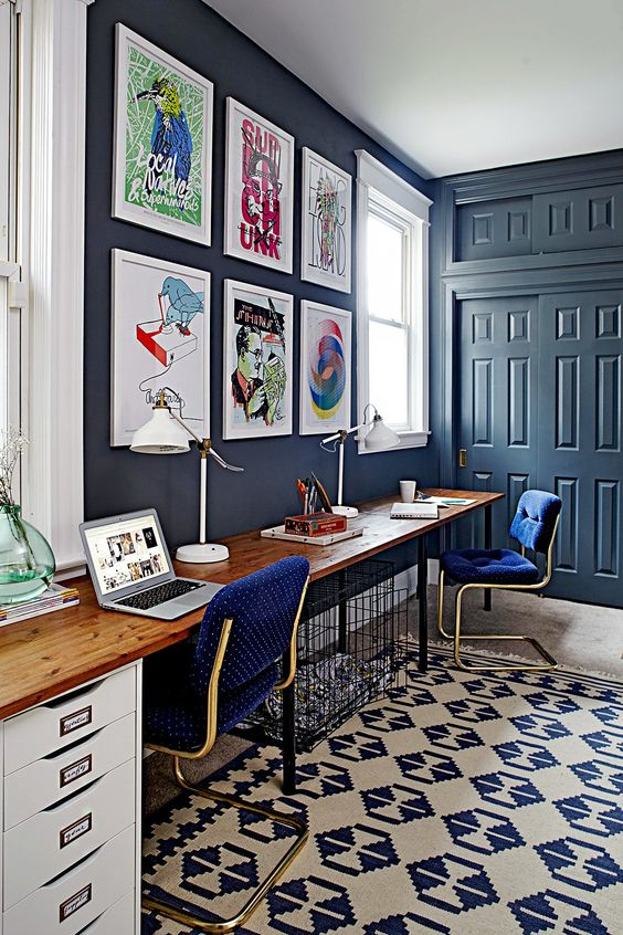 a bright home office with navy walls and doors, bright polka dot chairs and a crazy gallery wall and a printed rug