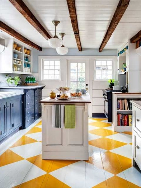 a bright kitchen with a geometric yellow and white floor, navy cabinets and dark stained wooden beams on the ceiling