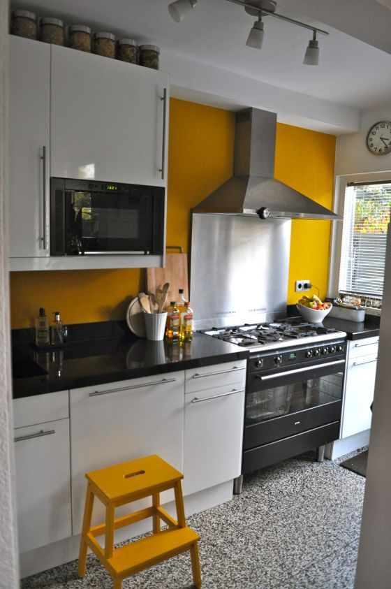 a bright kitchen with a mustard wall and a stool and black and white everything to calm that down a bit
