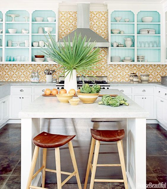 a bright tropical kitchen with a bold yellow tile backsplash, turquoise cabinets and touches of fresh greenery