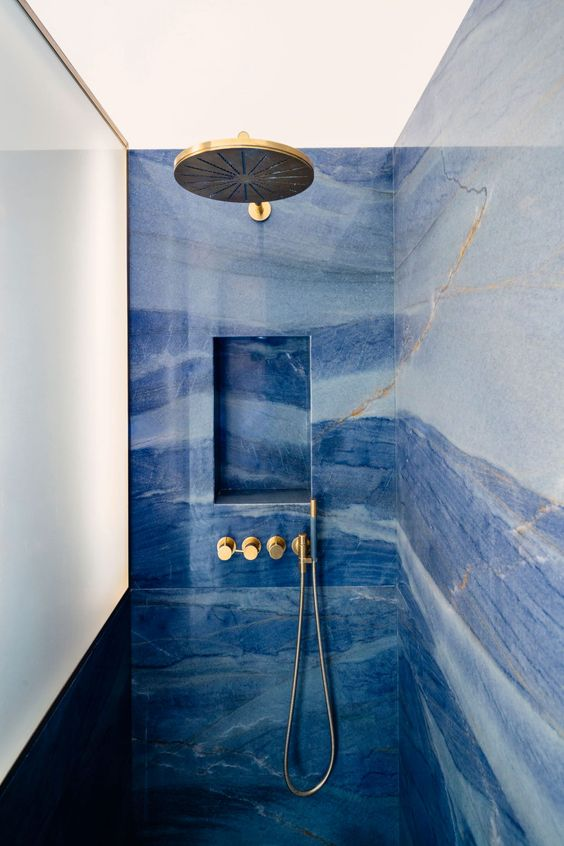 a catchy and bold blue bathroom done with watercolor tiles, gold fixtures and lamps is a stylish space