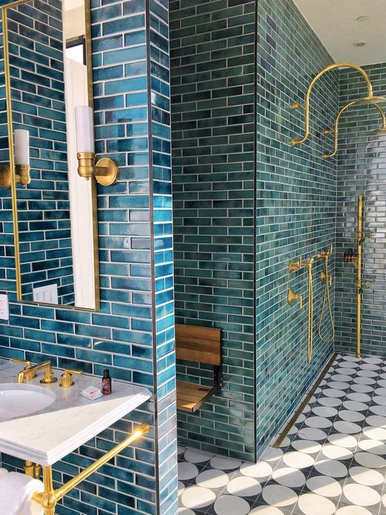 a catchy bathroom clad with blue tiles, finished off with gold fixtures and sconces looks wow