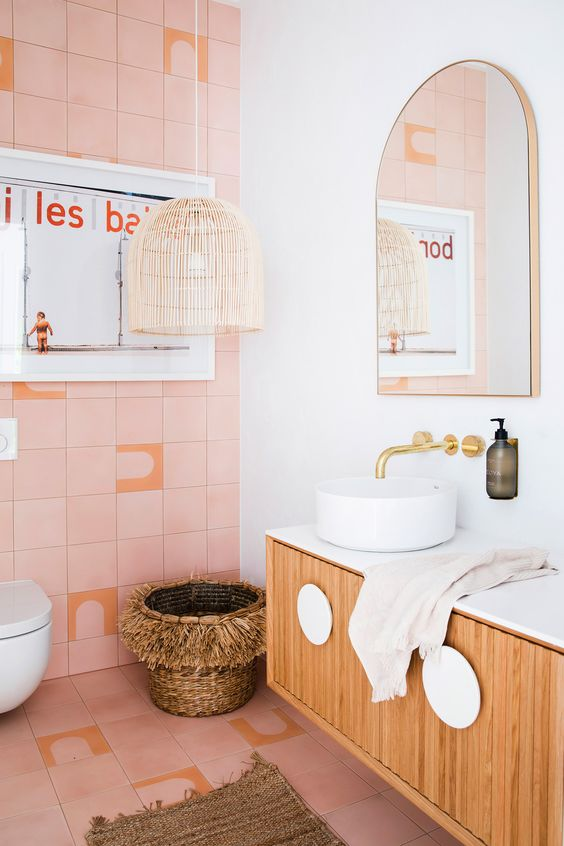 a catchy bathroom with pink tiles, a wicker lamp and basket, a floating vanity and gold fixtures for a glam touch