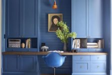 a catchy blue home office with large storage units, a built-in desk, a pendant lamp and greenery in a vase