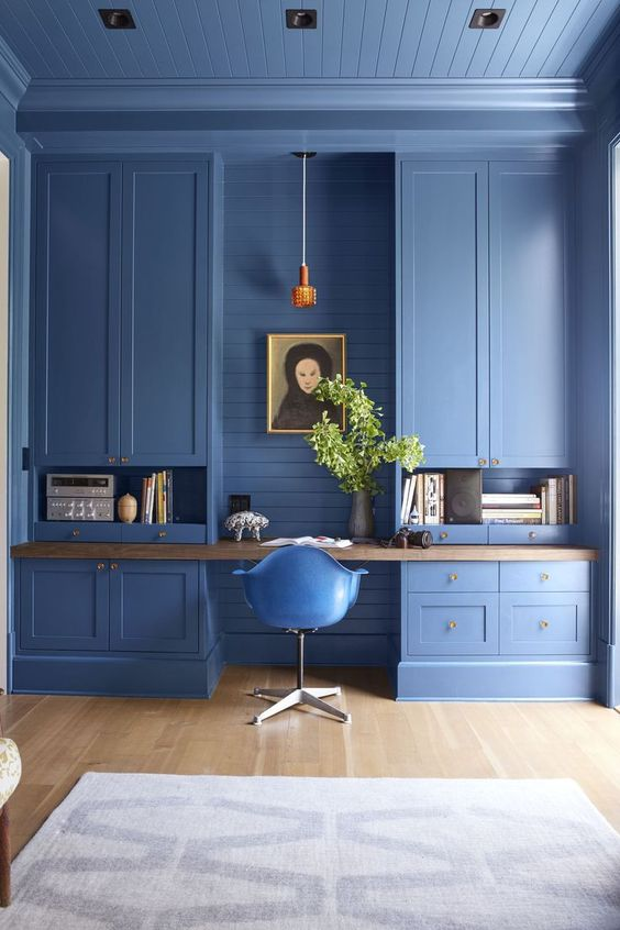 a catchy blue home office with large storage units, a built in desk, a pendant lamp and greenery in a vase