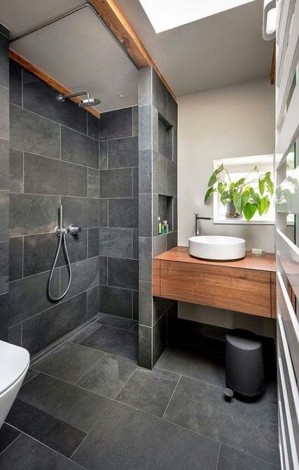 a catchy modern bathroom clad with graphite grey tiles, with a built-in vanity, potted greenery and a skylight