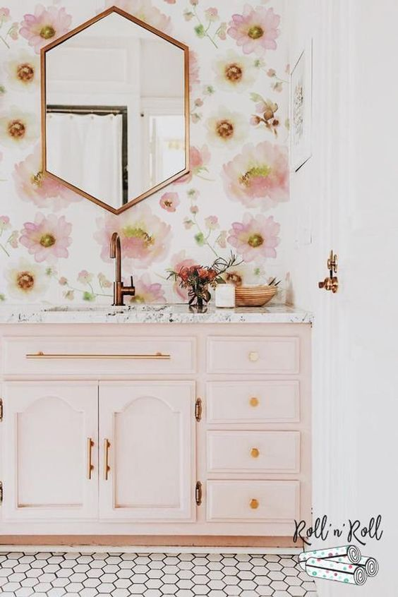 a chic and girlish bathroom with pink floral wallpaper, a light pink vanity and gold and copper fixtures and frames