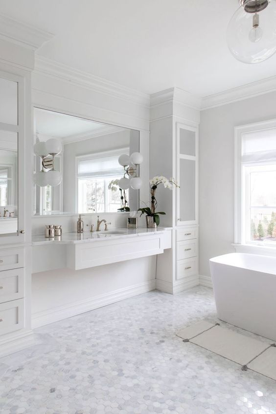 a chic and stylish white bathroom with marble hex tiles on the floor, a tub, a vanity with storage units and a mirror