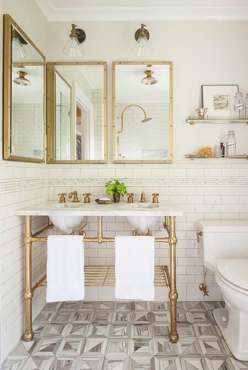 a chic bathroom with a retro touch, with gold framed mirrors, a gold vanity stand and gold shelves plus a mosaic floor