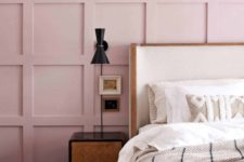 a chic bedroom with a pink paneled wall, a white bed, dark nightstands and sconces plus neutral embroidered bedding
