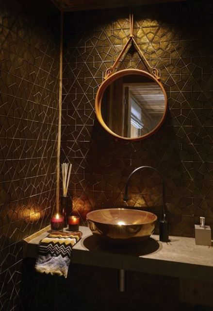 a chic black and gold bathroom with geometric tiles, gold accents and a gold frame mirror plus a unique sink