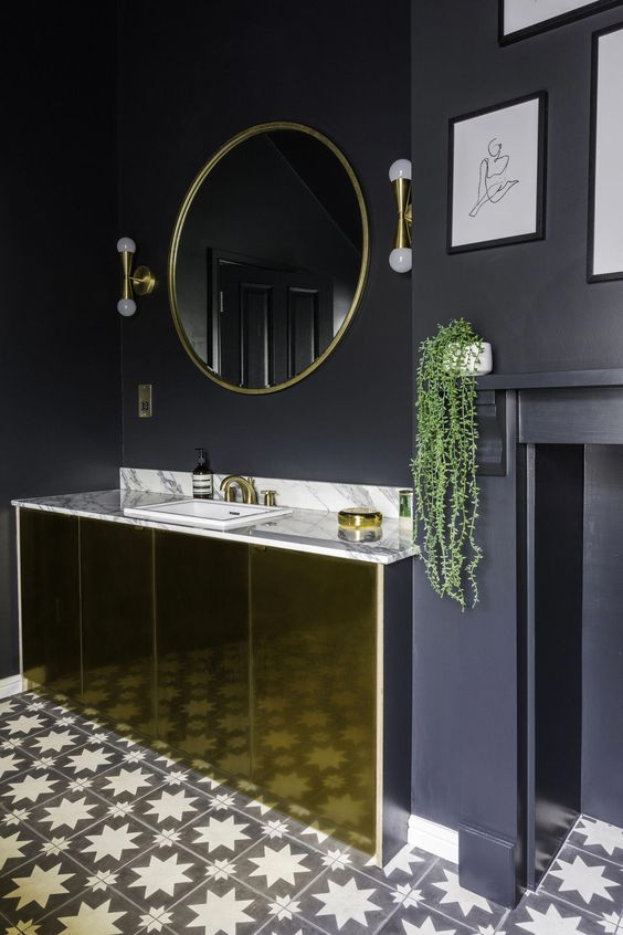 a chic black and gold bathroom with matte black walls, a polished gold vanity, gold fixtures and lamps and a mosaic floor
