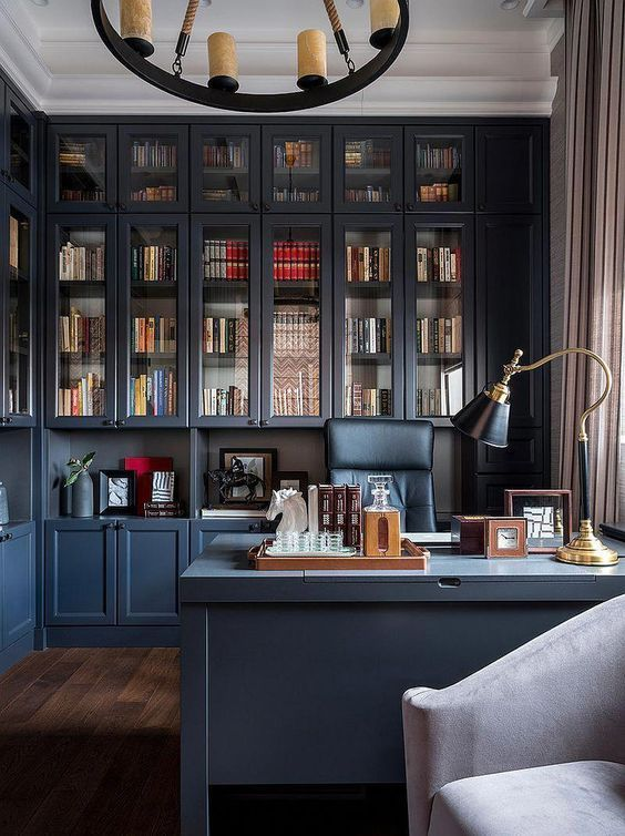 a chic blue home office, all the walls taken by storage units, a blue desk, a black chair and a catchy chandelier with candles
