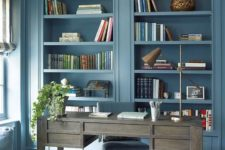 a chic blue home office with built-in storage units, a weathered wooden desk, gold and brass touches