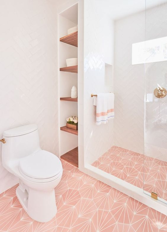 a chic contemporary bathroom with pink printed tiles on the floor, gold touches and fixtures plus simple white tiles on the walls