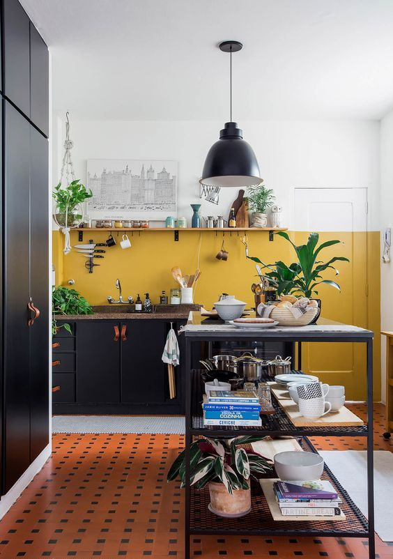 a chic contemporary kitchen done with mustard and white walls, with black cabinetry, a kitchen island and a black lamp